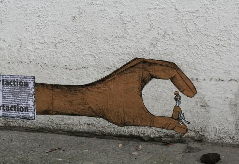 Graffiti of hand pinching a tiny girl.